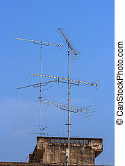 TV antenna on the roof and blue sky background