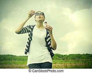 Girl blowing soap bubbles - Young girl blowing soap bubbles...