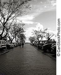Parking lot with cars, trees and people passing by.