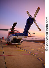 offshore oil rig helicopter in the apron next to runway