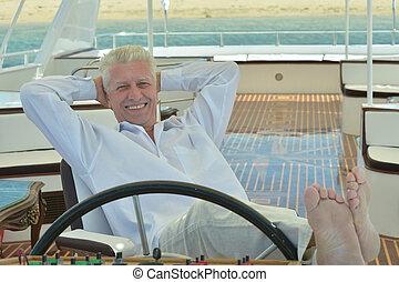 Senior man having boat ride - Amusing elderly man have a...