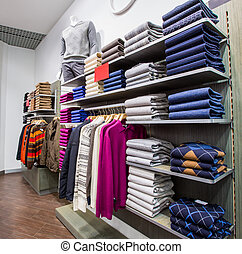 Clothing on hangers in shop - Fashionable clothing on...