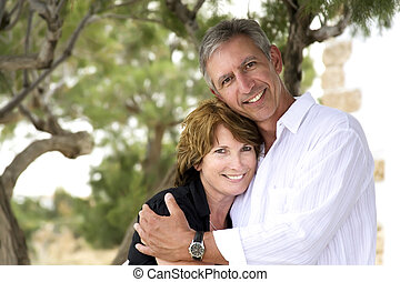 beautiful mature couple standing and holding each other...