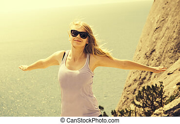 Young Woman happy smiling hands raised with sea on background Summer vacations and Lifestyle concept retro colors
