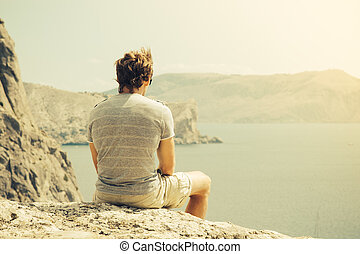 Young Man relaxing on rocky cliff  Sea and mountains on background Lifestyle Summer vacations concept retro colors