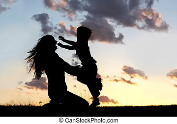 Silhouette of Child Running to Hug Mother at Sunset - a...