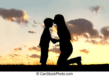 Mother Lovingly Kissing Little Child at Sunset - Silhouette...
