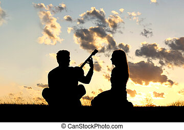 Silhouette of Couple Playing Guitar at Sunset - A silhouette...