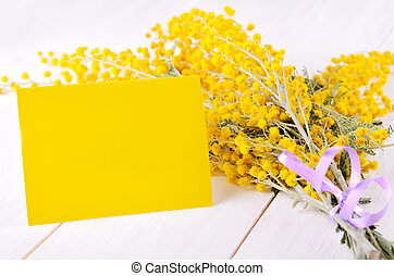 Empty card with mimosa flowers, on white wooden background