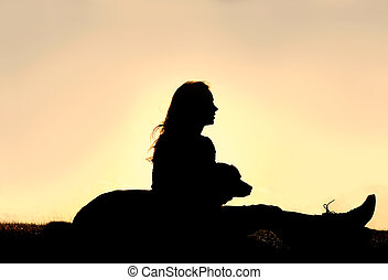 Silhouette of Girl Sitting OUtside with Large Dog -...