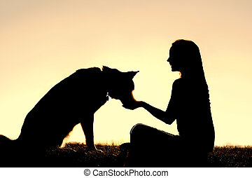 Woman Feeding Pet Dog Treats Silhouette - A silhouette of a...