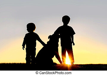 Silhouette of Young Children with Dog - A silhouette of two...