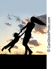 Silhouette of Mother Spinning and Dancing with Child at Sunset