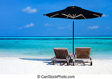 Idyllic tropical beach at Maldives - Chairs and black...
