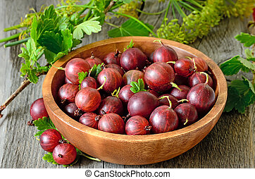 Gooseberries in bowl on wooden table
