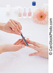 Preparing nails for manicure. Close-up of beautician...