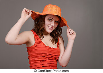 teen girl hold orange straw hat