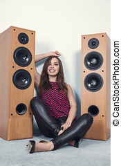 Young woman listening music in front of big speakers