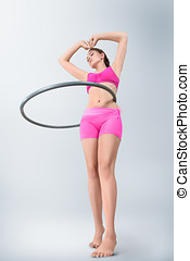 Young woman rotating hula hoop - Young fitness sport woman...