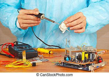 Serviceman solder electronic hardware in service workshop -...