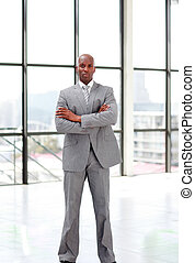 Serious businessman with folded arms looking at the camera