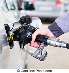 Petrol being pumped into a motor vehicle car. - Petrol or...