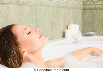 Woman in bath relaxing - Young beautiful woman relaxing in a...
