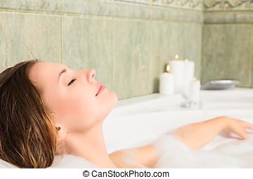 Woman in bath relaxing - Young beautiful woman relaxing in a...
