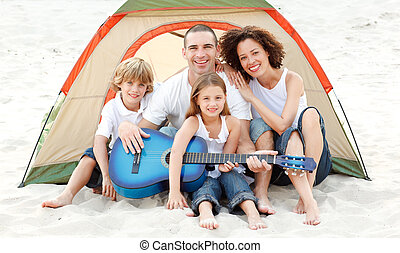 Family camping on beach playing a guitar - Happy family...