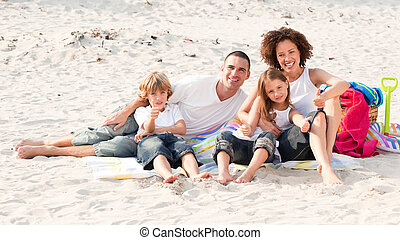 Family playing sitting on a beach - Happy family sitting on...