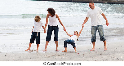 Family walking on a beach - Young family walking on a beach