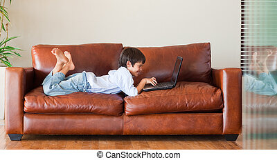 Young kid with a laptop on the couch