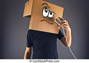 Man with cardboard box on his head using tin can telephone...
