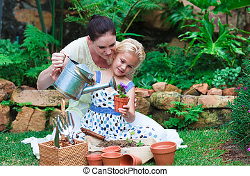 Mother and daughter planting in their garden - Smiling...