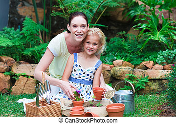 Young mother and daughter planting flowers - Happy young...