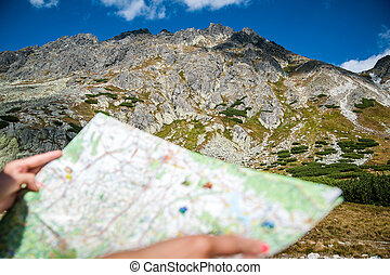 tourist in mountains read the map