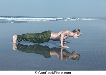 Young man doing push ups during fitness training on sea...