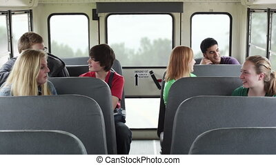 Kids on school bus - High school kids talking to each other...
