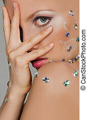 Sensual woman in precious stones covered with palm