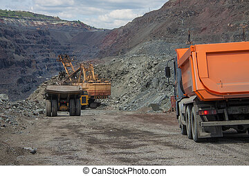 Mining - Heavy mining trucks being loaded with iron ore on...