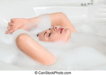 Young beautiful woman relaxing in a bath