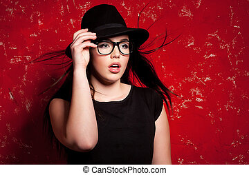 Glamour fashion model. Beautiful young woman in hat and glasses posing against red background