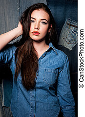 Following her personal style. Close Up image of beautiful young woman in jeans shirt wear holding hand on head