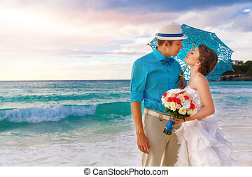 Wedding Bbride and groom on the tropical coast at sunset