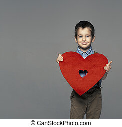 Portrait of a small boy presenting heart