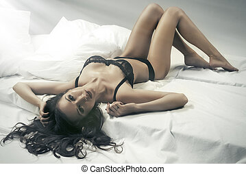 Sexy slim brunette woman posing in bed, looking at camera. Lady wearing sensual lingerie.