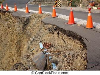 Road Damaged by Landslide - Red and white traffic cones mark...