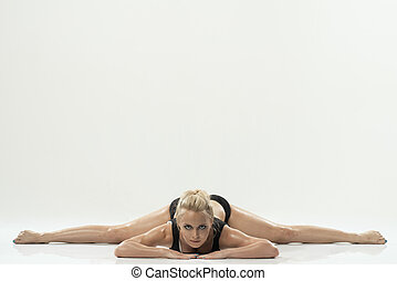 Young attractive female fitness model performing a twine