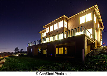 House with lights on. NIght view - Big modern house with...