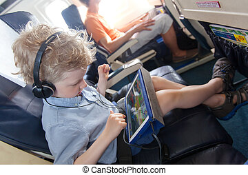 boy in the plane - little boy playing at tablet waiting in...